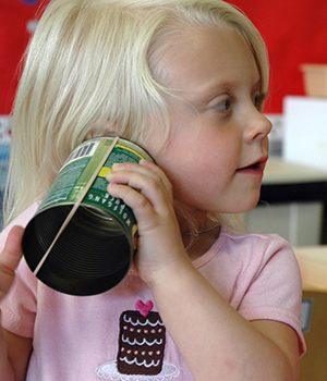 children exploring sound with tin can and rubber bands