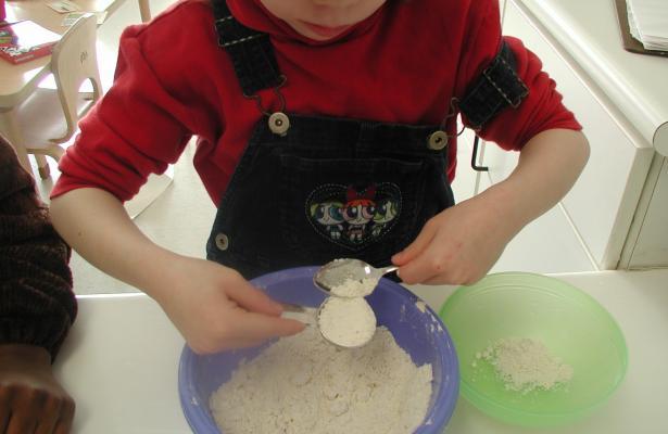 Child leveling flour
